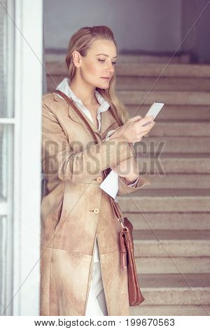 Serious business woman reading message on the phone, female at work, smart and busy office worker