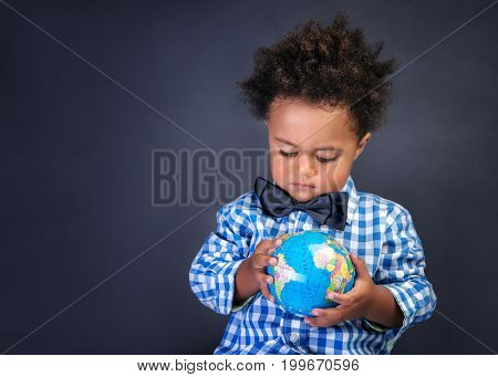 Happy preschooler discovering world, african boy looking on little globe, copy space, geography lesson, back to school concept