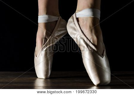 Close-up classic ballerina's legs in pointes on the black wooden floor.