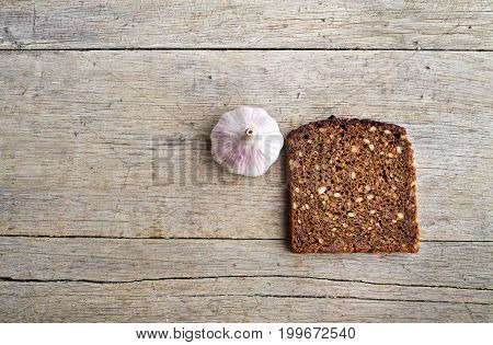Slice of whole grain brown bread and pungent garlic on wooden table.