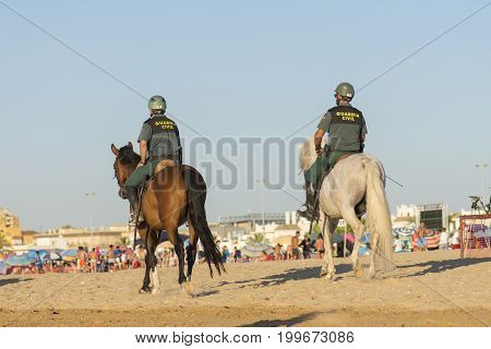 Spanish civil guard, watching on the beach of Sanlúcar de Barrameda, Cadiz during the horse races that are celebrated every year in the month of August on this beach, photo taken on August 3, 2017