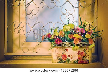A bouquet of bright artificial flowers in a pot is located on the background of a glass window. Creative image retro style