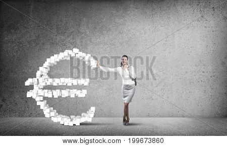 Young confident businesswoman leaning on big euro sign