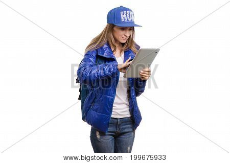 Beautiful young girl travels with a backpack and tablet on a white background isolated