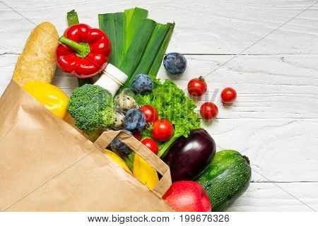Full paper bag of different health food on white wooden background. Top view. Flat lay