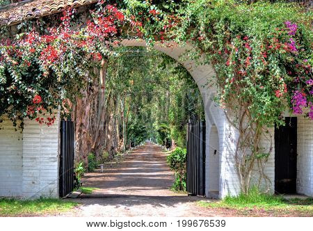 Entrance to an old hacienda converted to a public  restaurant, with a gate, flowers and an old dirt road, Pichincha Province, Ecuador.