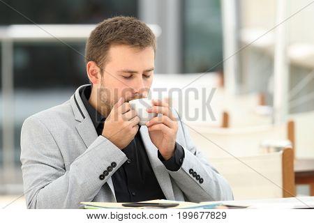 Executive drinking enjoying coffee break sitting in a bar