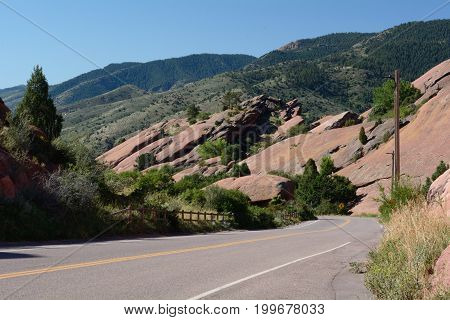 Landscape and road within Red Rocks Park in Colorado with view of Rocky Mountain foothills