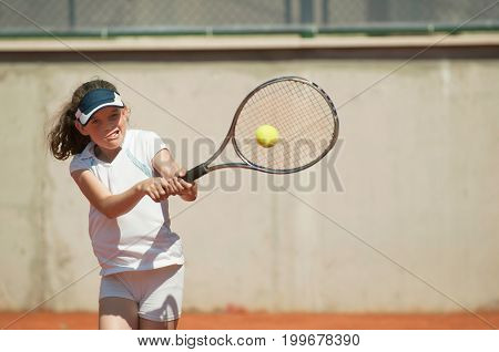 Young girl hitting the ball with backhand slice toned image
