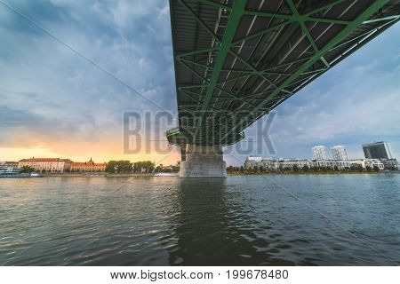 By the River under the Bridge. Skyline of Bratislava Slovakia at Sunset in Background.