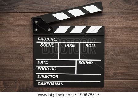 vintage classic clapper board. clapper board on wooden background. top view of black wooden clapper board. new blank clapper board on brown table