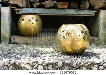 golden candle holders on textured concrete with wood in back
