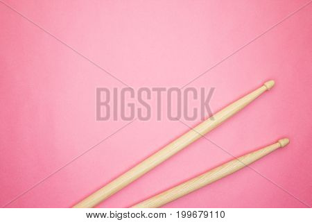 pair of wooden drumsticks on pink background