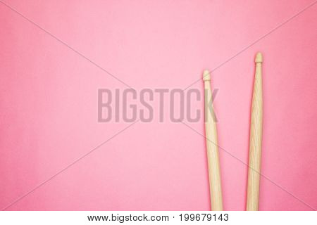 pair of wooden drumsticks on pink background. top view of drumsticks. pair of drumsticks with copy space. wooden drumsticks on the table
