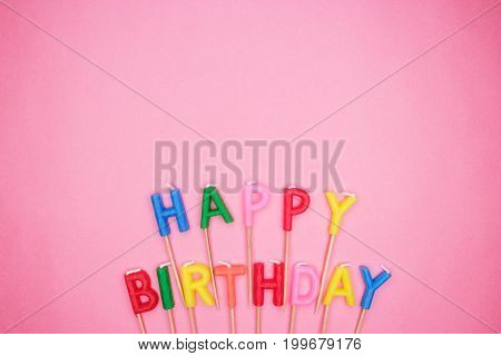 colorful letter-shaped happy birthday candles. birthday candles on pink background. colorful letter-shaped birthday candles with copy space. top view of birthday candles on the table