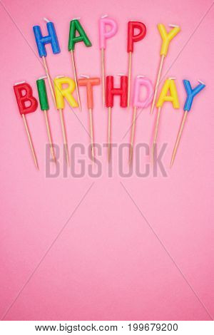colorful letter-shaped happy birthday candles on pink background