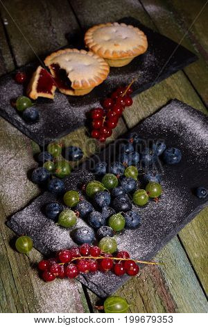 Berries and cookies with jam. View from above. Gooseberries, blueberries and currants on a wooden table.