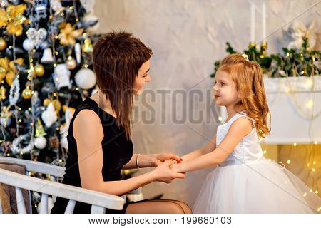 Happy mother and child holding hands and looking at each other at Christmas tree.