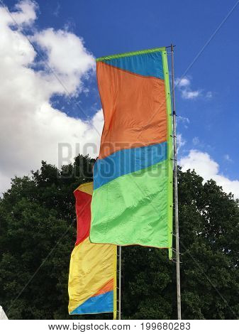 Two colorful flags flying at a festival on a sunny day with clouds in the sky and space for text.