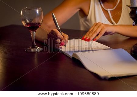 writing a letter while drinking wine, love or bussines