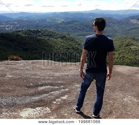 Young man stands at the top of a mountain in Monte Verde Minas Gerais Brazil.