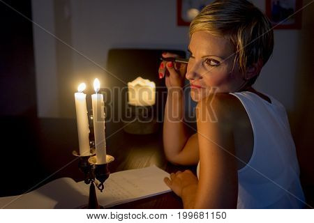 woman is thinking what to write under candle light