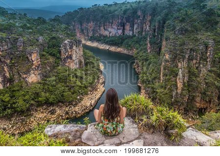 Girl Sits On A Rock Overlooking A Canyon With A River On The Bottom And Rocky Walls Covered By Green