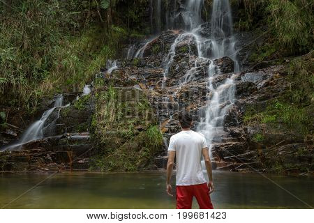Man At Waterfall. Beautiful Waterfall In The Forest. Natural Water Spring Waterfall.