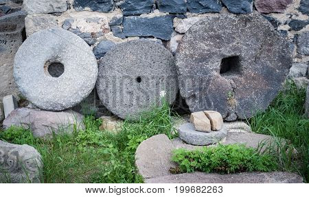 Stone granite wheels with rusted metal rim isolated on green grass near wall.