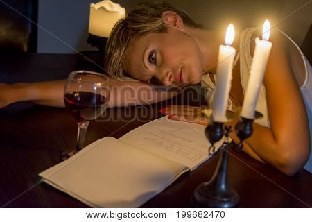 woman writing a letter under candle light