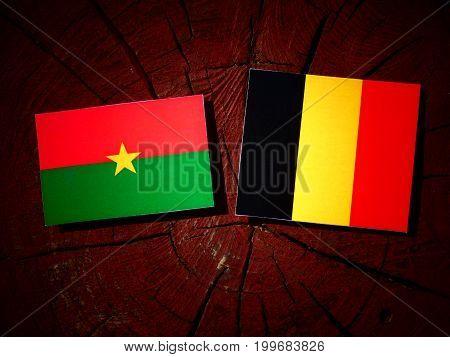 Burkina Faso Flag With Belgian Flag On A Tree Stump Isolated