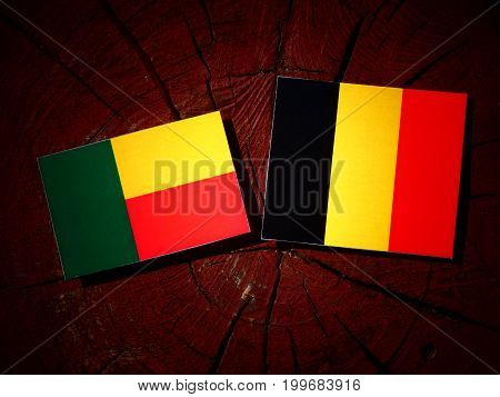 Benin Flag With Belgian Flag On A Tree Stump Isolated