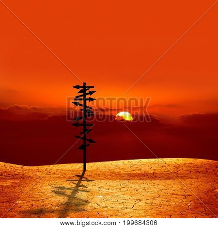 conceptual image of silhouetted directional sign on cracked dry landscape over sunset