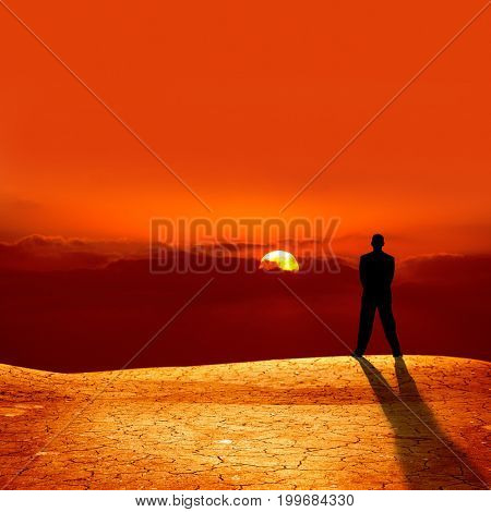 conceptual image of silhouetted businessman on cracked dry landscape watching sunset