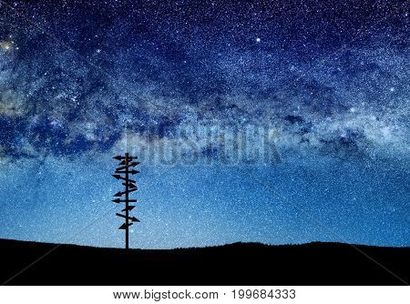 conceptual image of silhouetted directional sign and abstract lights of universe.