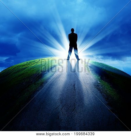 conceptual image of silhouetted businessman on empty road over cloudy sky with beam of light