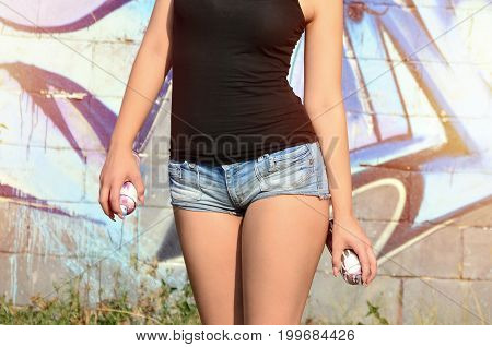 A Young And Beautiful Sexy Girl Graffiti Artist With A Paint Spray Stands On The Wall Background Wit