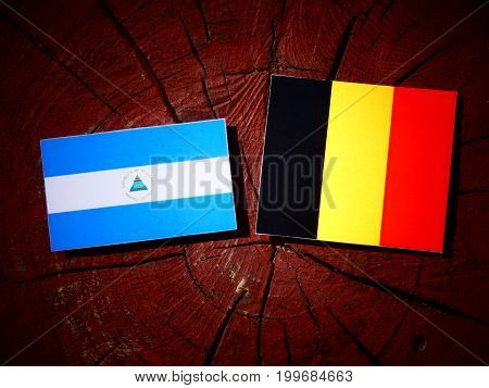 Nicaraguan Flag With Belgian Flag On A Tree Stump Isolated