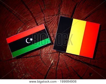 Libyan Flag With Belgian Flag On A Tree Stump Isolated