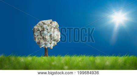Conceptual image of money tree on green landscape
