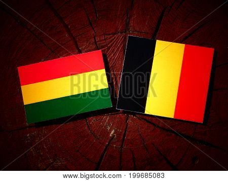 Bolivian Flag With Belgian Flag On A Tree Stump Isolated