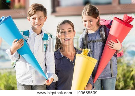 Mother and children on first day at school with candy cones