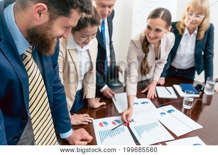 Multi-ethnic team of five dedicated specialists smiling while analyzing various charts with positive statistics about the profit and the development of the company