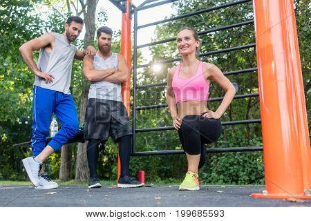 Full length of a ravishing young woman smiling while doing Bulgarian squats during lower-body workout routine in the admiration of her male friends outdoors