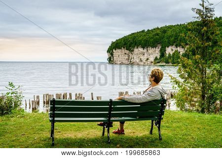 Woman is relaxing on a bench in Fayette State Park in Upper Peninsula, Michigan