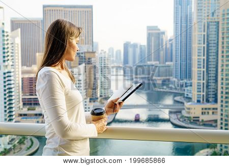 Mature woman is reading a book on her balcony in a highrise building