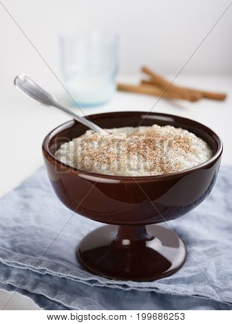 Rice pudding topped with cinnamon powder and cinnamon sticks
