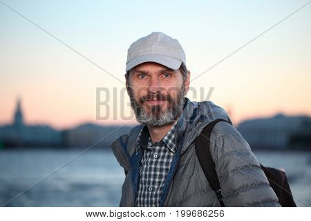 Mature tourist with backpack on the embankment of Neva river in St. Petersburg, Russia