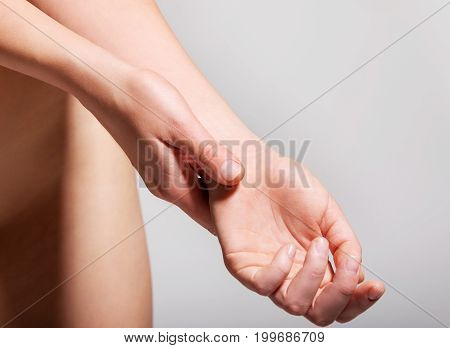 Close up of woman holding her wrist. Pain concept.