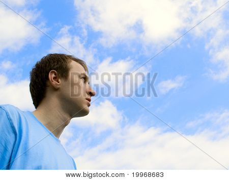 The young man looks at the blue sky